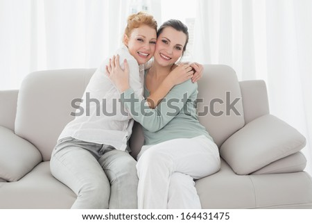 Portrait of cheerful young female friends embracing in living room at home