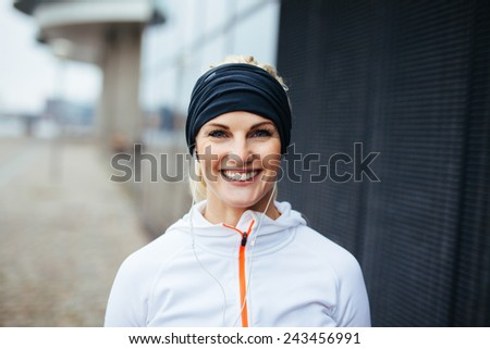Portrait of cheerful young fitness woman. Smiling young female athlete in sports wear outdoors. - stock photo