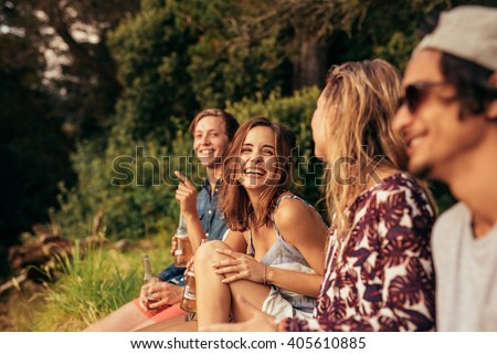 Portrait of cheerful young friends hanging out with beers. Group of friends sitting outdoors and having fun. - stock photo