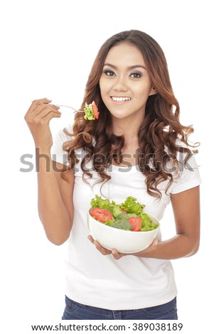 portrait of cheerful young girl eating healthy vegetables salad isolated on white background