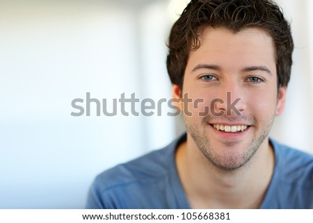 Portrait of cheerful young guy with blue eyes - stock photo