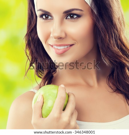 Portrait of cheerful young lovely brunette woman in fitness wear with apple, outdoors. Healthy lifestyle, beauty and dieting concept. - stock photo