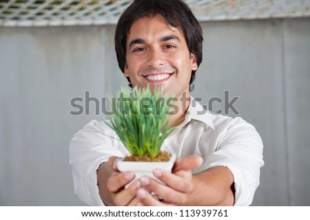 Portrait of cheerful young man holding small plant - stock photo