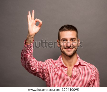 Portrait of cheerful young man showing okay gesture in studio. Happy man smiling for the camera over grey background. - stock photo