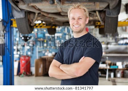 Portrait of cheerful young mechanic with arms crossed standing in his auto repair shop - stock photo