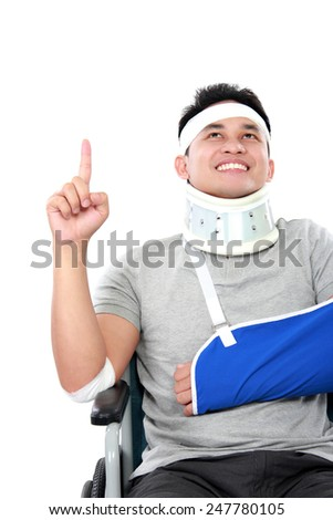 portrait of cheerful young men with broken arm pointing upwards - stock photo