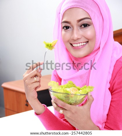 portrait of cheerful young muslim woman eating healthy breakfast on bed - stock photo