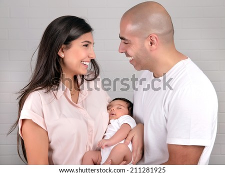 Portrait of cheerful young parents holding on hands cute newborn daughter, healthy childhood, happy parenthood concept  - stock photo