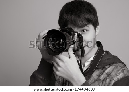Portrait of cheerful young photographer with a professional camera. Isolated on a light background - stock photo