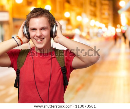 portrait of cheerful young student listening music with headphones at night city