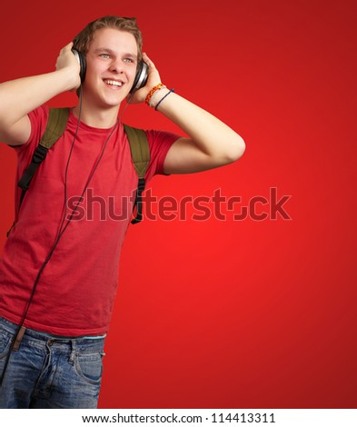 portrait of cheerful young student listening music with headphones over red