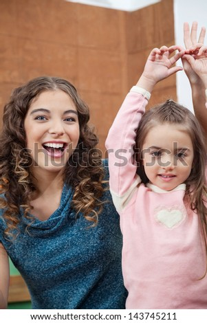 Portrait of cheerful young teacher and little girl with hands raised in classroom - stock photo