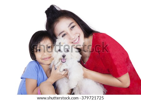 Portrait of cheerful young woman and little girl embrace a maltese dog together while smiling at the camera - stock photo