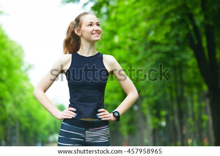 Portrait of cheerful young woman before a running session. - stock photo