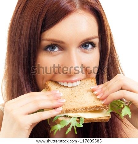 Portrait of cheerful young woman eating sandwich with cheese, isolated over white background - stock photo