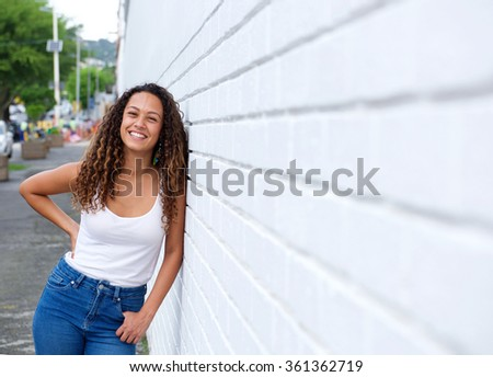 Portrait of cheerful young woman in leaning on a wall outdoors. - stock photo