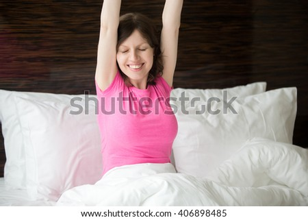 Portrait of cheerful young woman lying in bed after waking up and stretching with pleasure. Beautiful female model relaxing in the morning with closed eyes - stock photo