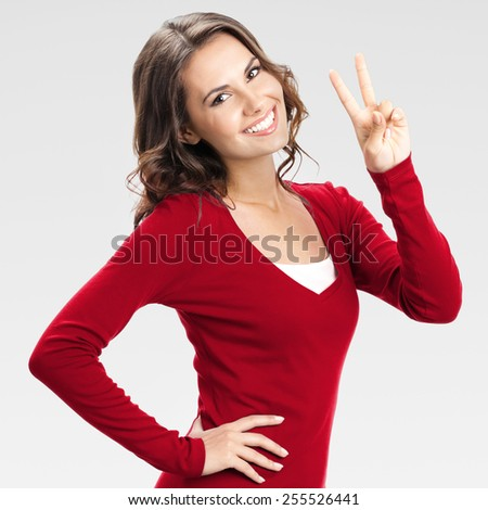 Portrait of cheerful young woman showing two fingers or victory gesture, over grey background - stock photo