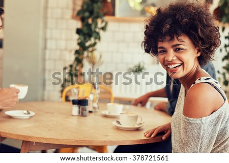Portrait of cheerful young woman sitting at a cafe table with friends in background - stock photo