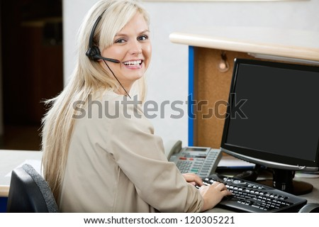 Portrait of cheerful young woman using computer at reception desk - stock photo
