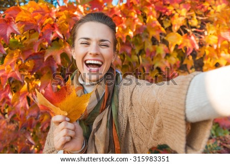 Portrait of cheerful young woman with autumn leafs in front of foliage making selfie - stock photo