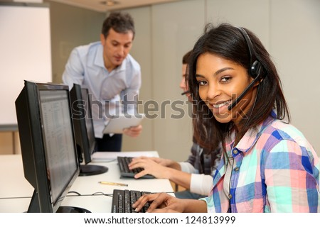 Portrait of cheerful young woman with headset on - stock photo