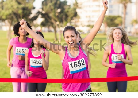 Portrait of cheering brunette winning breast cancer marathon in parkland - stock photo