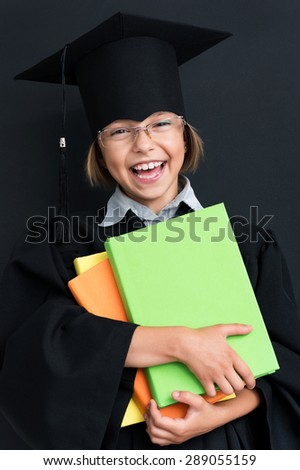 Portrait of cheering girl wearing black graduation gown holding books at the black chalkboard in classroom. - stock photo