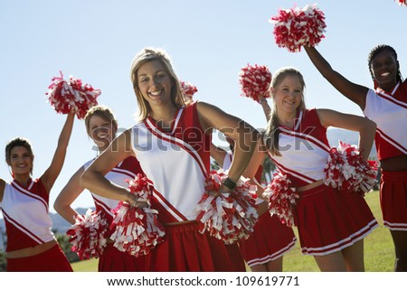 Portrait of cheerleaders with pom-pom on field - stock photo
