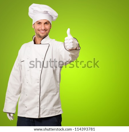 Portrait Of Chef Showing Thumb Up Sign On Green Background - stock photo