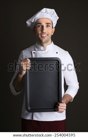 Portrait of chef with oven pan in hands on dark background - stock photo