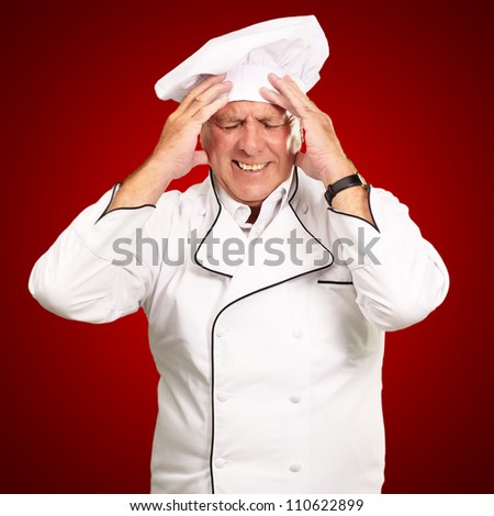 Portrait Of Chef With Painfully Head On Red Background - stock photo