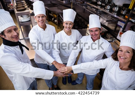 Portrait of chefs team putting hands together and cheering in a commercial kitchen - stock photo