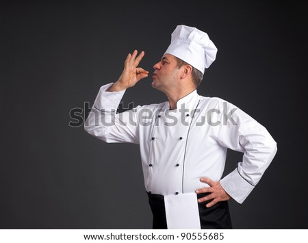 Portrait of chief cook with hand sign on grey background - stock photo