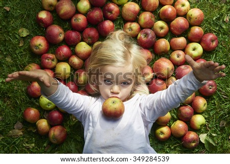 Portrait of child blond young girl lying and eating on the grass with apples background