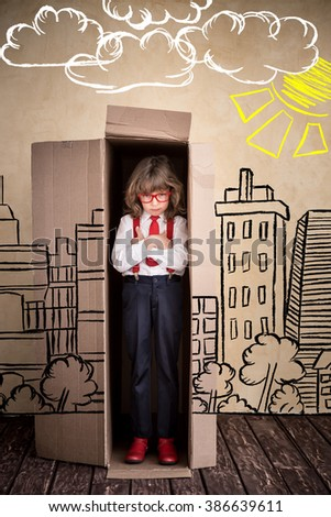Portrait of child businessman in cardboard box. Think outside the box business concept - stock photo