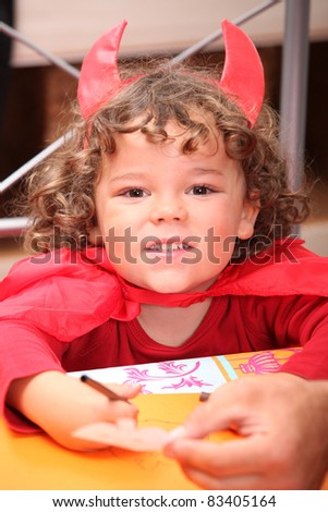 Portrait of child dressed up as devil - stock photo