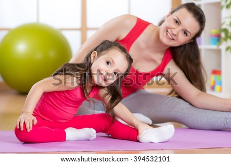 Portrait of child girl and mother doing physical exercise at home - stock photo