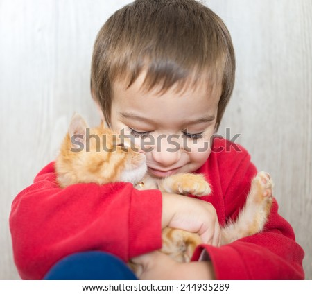 Portrait of child holding yellow kitty cat - stock photo