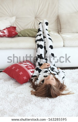 Portrait of child in soft warm cow print pajamas playing at home - stock photo