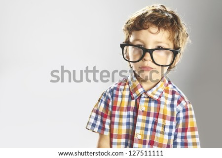 Portrait of child isolated on grey background. Child with plaid shirt and glasses - stock photo