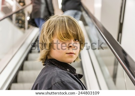portrait of child on moving staircase in the shopping center - stock photo