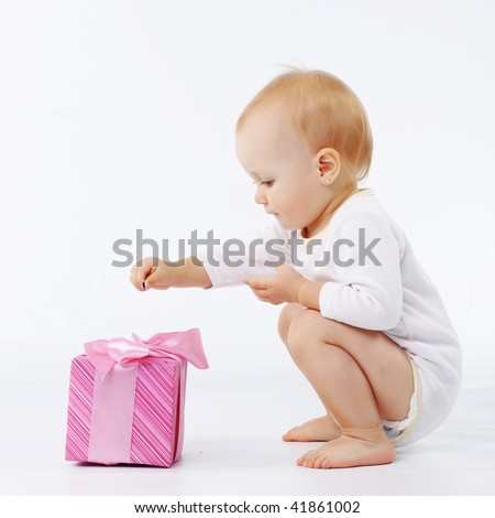 Portrait of child opening gift box in white studio - stock photo