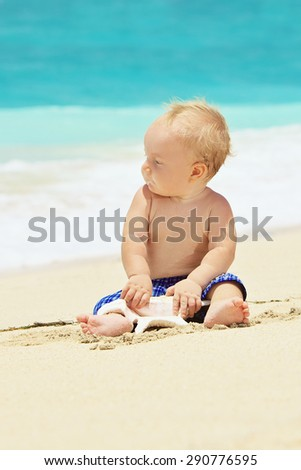 Portrait of child sitting and playing alone with sea shell with fun on balinese sand ocean beach before swimming. Family lifestyle, water leisure on summer vacation with baby on tropical Bali island - stock photo