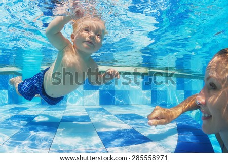 Portrait of child swimming with fun underwater in pool with diving cheerful mother. Healthy lifestyle, active parenting, and children water sports activity during summer family vacation with baby boy - stock photo