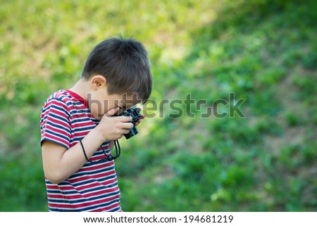 Portrait of child with digital compact camera outdoors. - stock photo