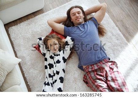 Portrait of child with father wearing pajamas lying down on a carpet - stock photo