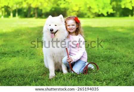 Portrait of child with white Samoyed dog on the grass in sunny summer day - stock photo