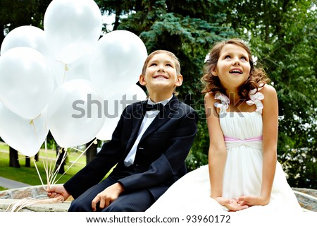Portrait of children bride and groom with balloons sitting in park - stock photo