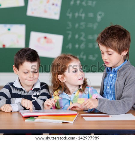 Portrait of children having a group work at the classroom - stock photo
